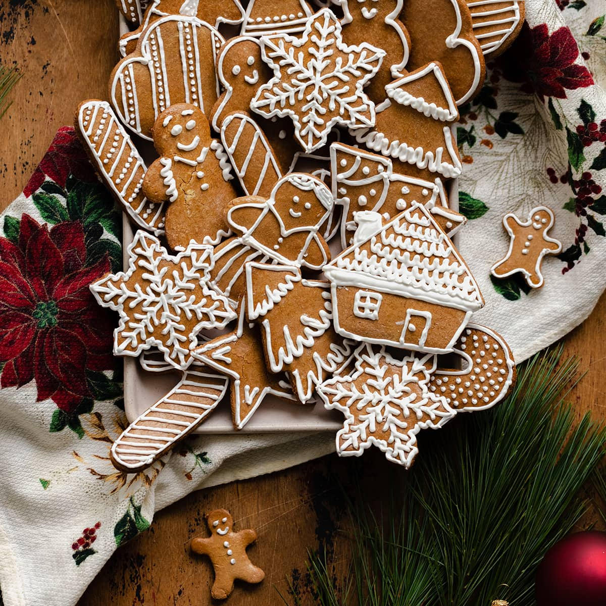 Czech Gingerbread Cookies on a plate with a Christmas tea towel underneath. On a light wooden background with pine branches and Christmas decorations around the plate.