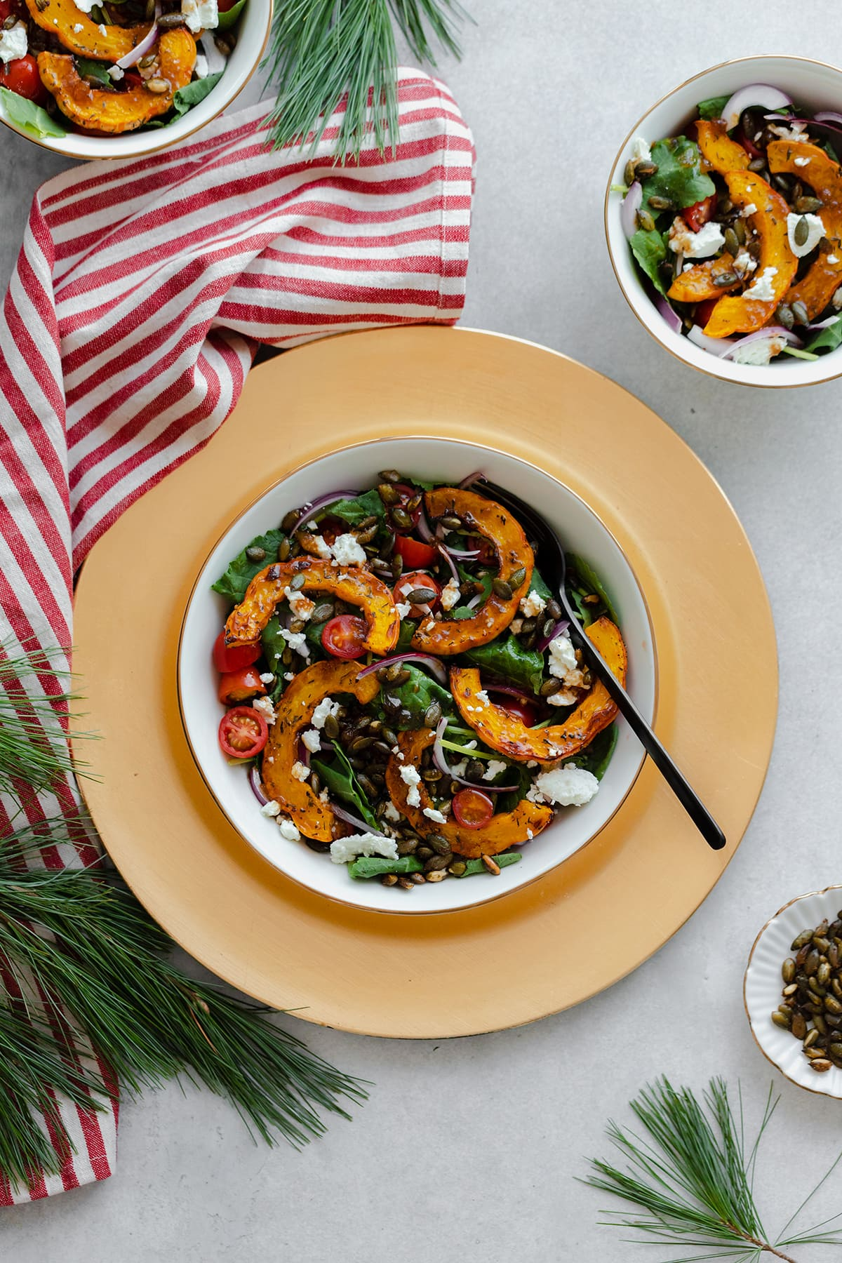 A photo of delicata squash salad in a white bowl with a black fork. Bowl on a decorative gold plate with a red and white tea towel on the left and a decorative some decorative pine branches.