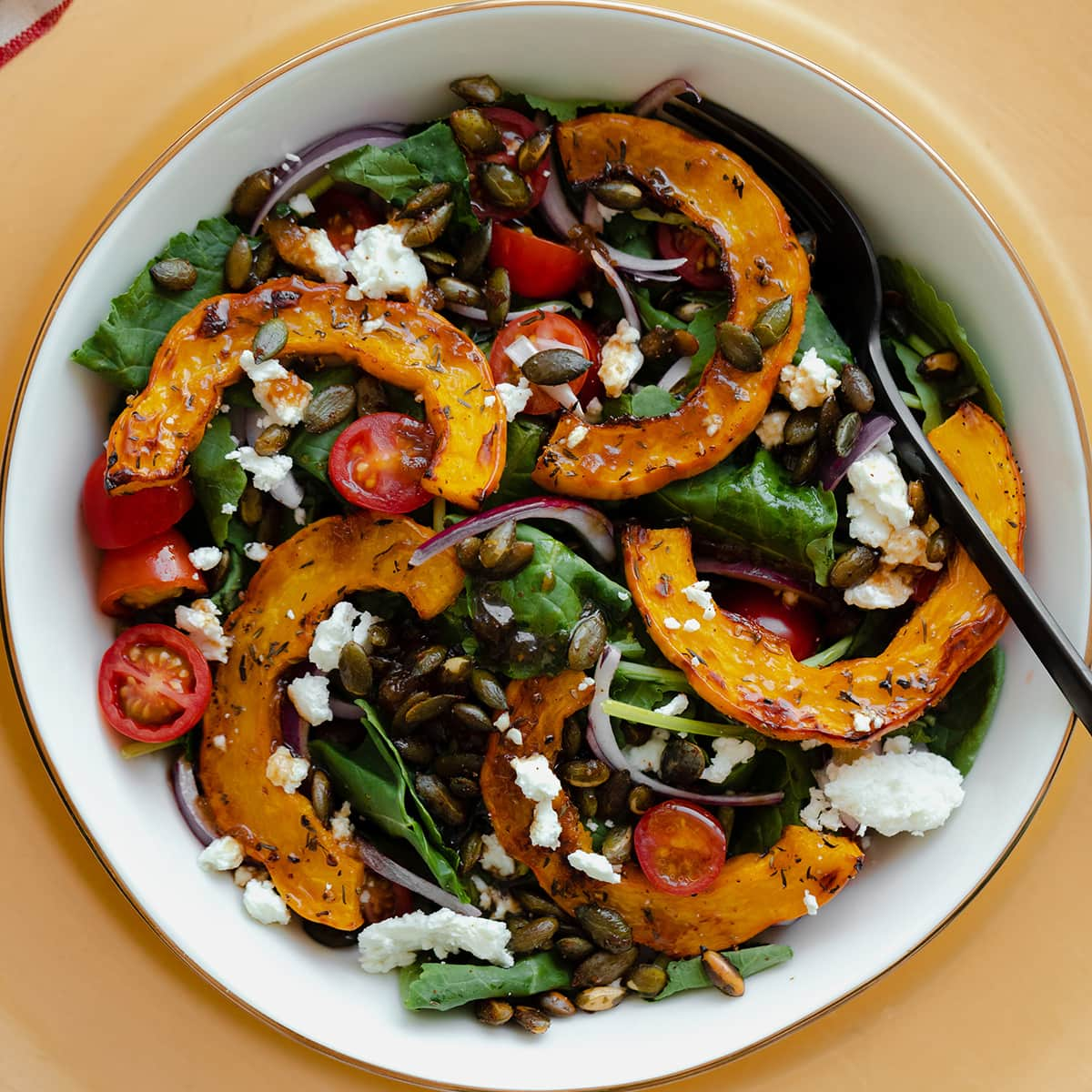 A close up of delicata squash salad in a white bowl on a decorative gold platter