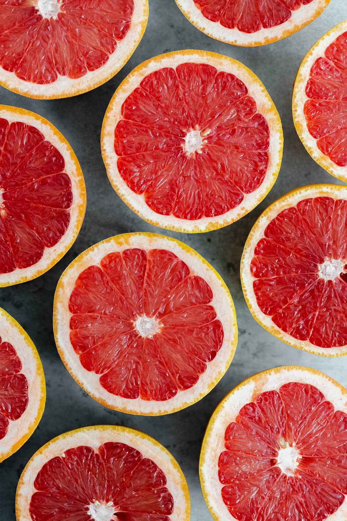 Grapefruits cut in half, laid out evenly cut side up on a gray background.