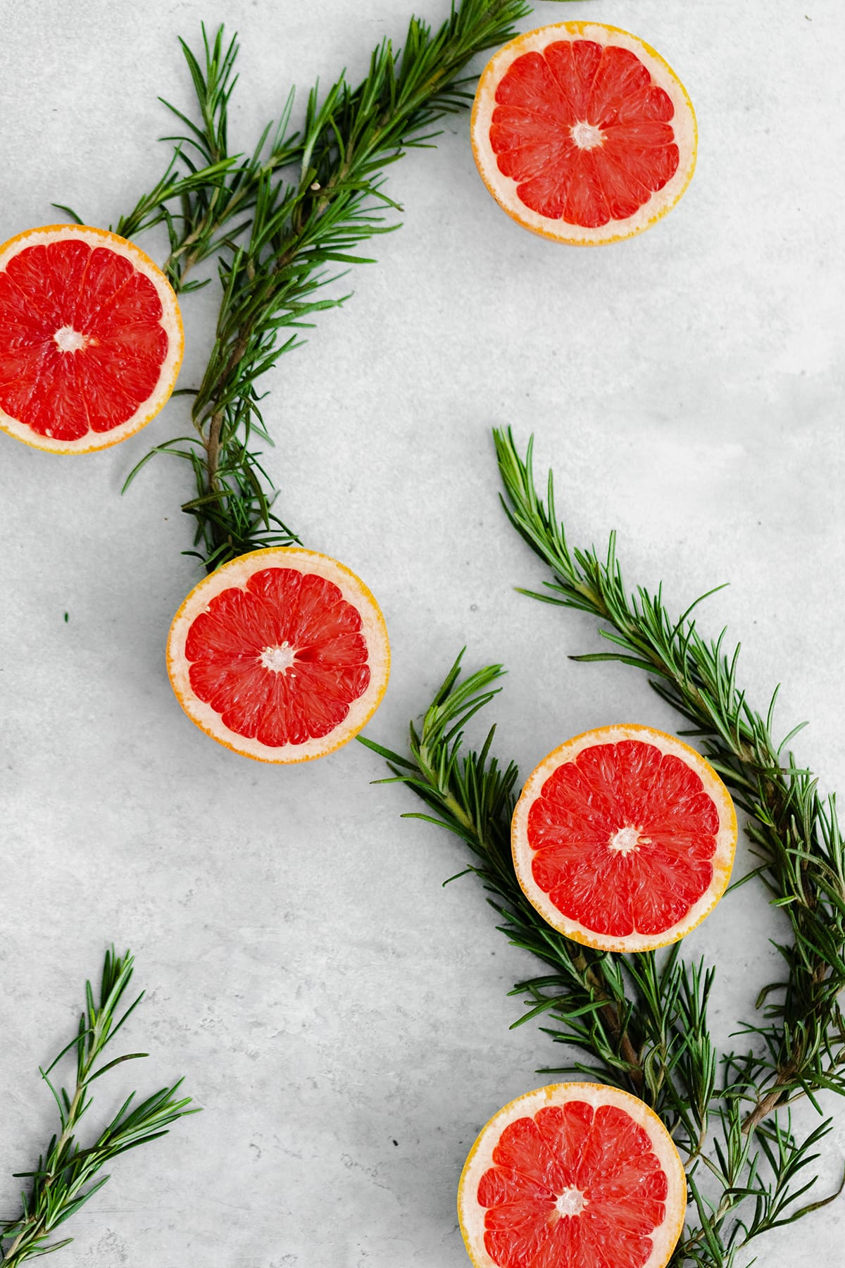 Grapefruits cut in half, laid out in an S shape with fresh rosemary connecting each piece. Cut side up on a gray background.