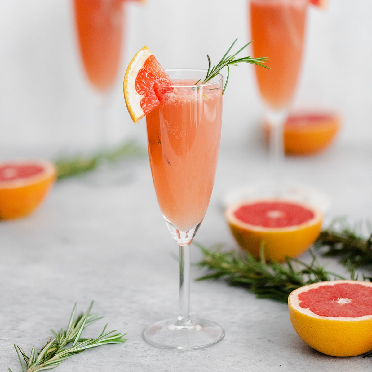 Grapefruit Mimosa in 3 flute glasses garnished with fresh rosemary and a quarter of a slice of grapefruit on the rim. Grapefruits as decoration in the background.