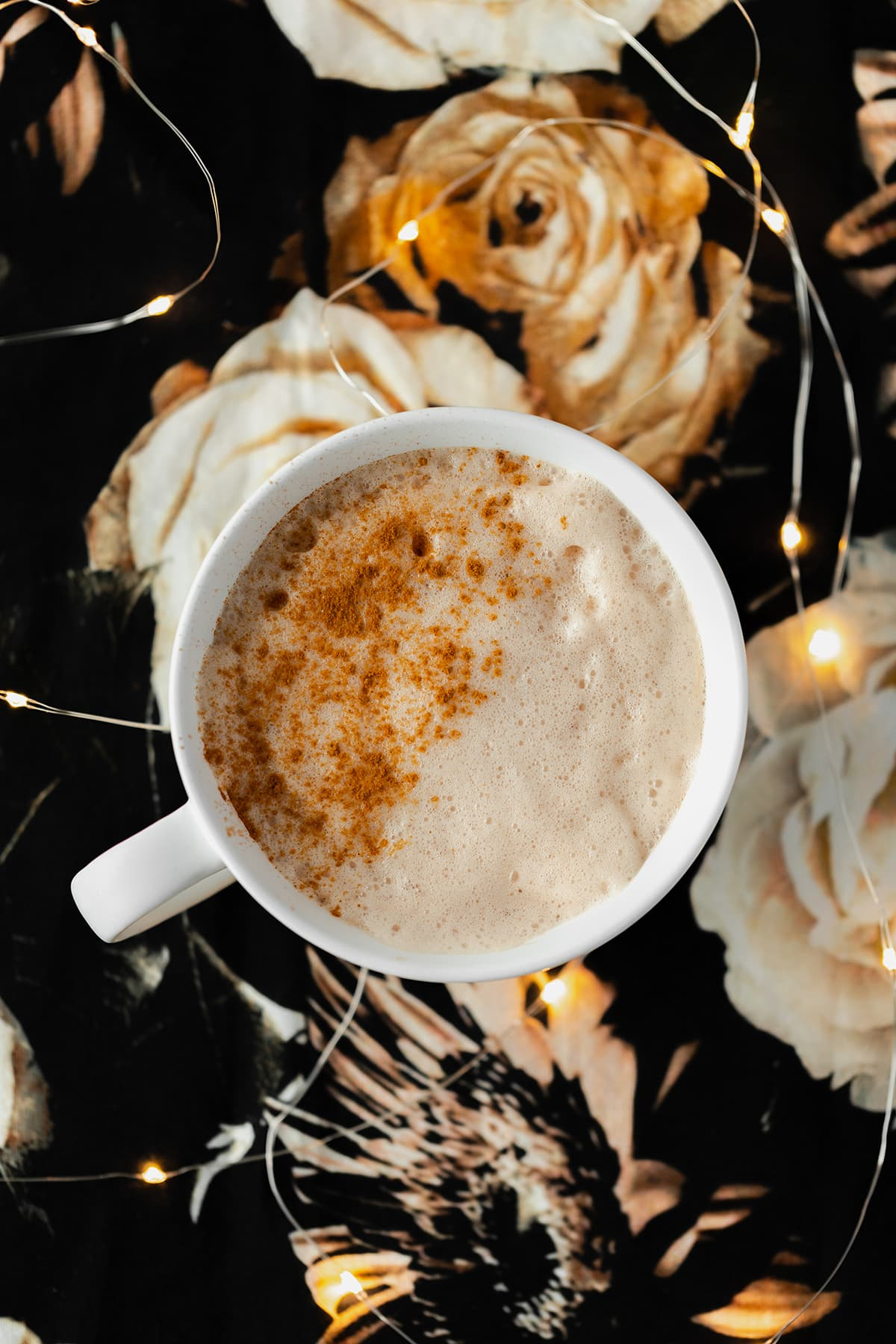 Blossoming Rose Tea Latte in a white mug with a light dusting of cinnamon on the left side. On a black table cloth with beige rose print. Fairy lights around mug.
