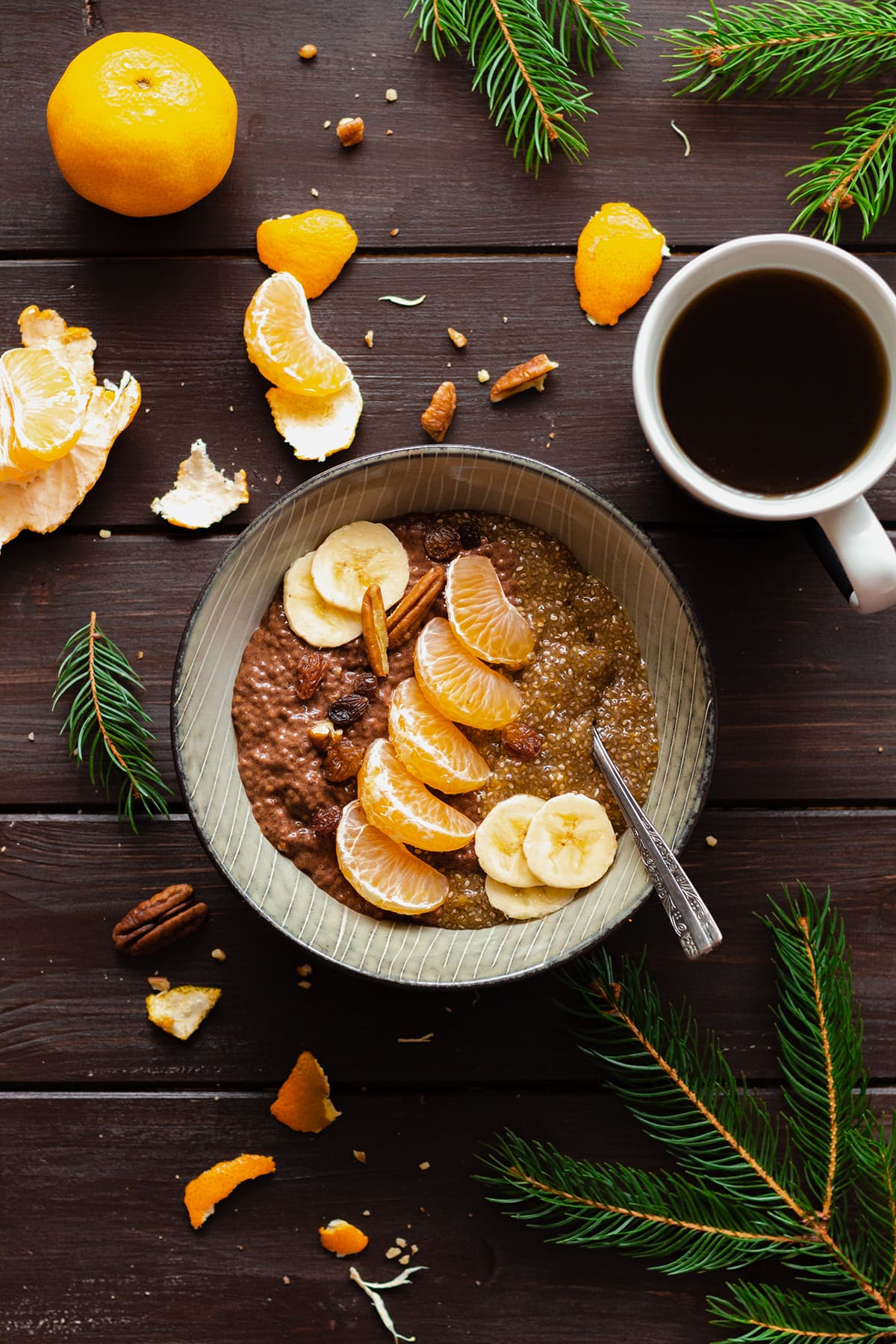 Tangerine Chocolate Chia Pudding in a bowl on a dark wooden table with a cup of coffee on the left.