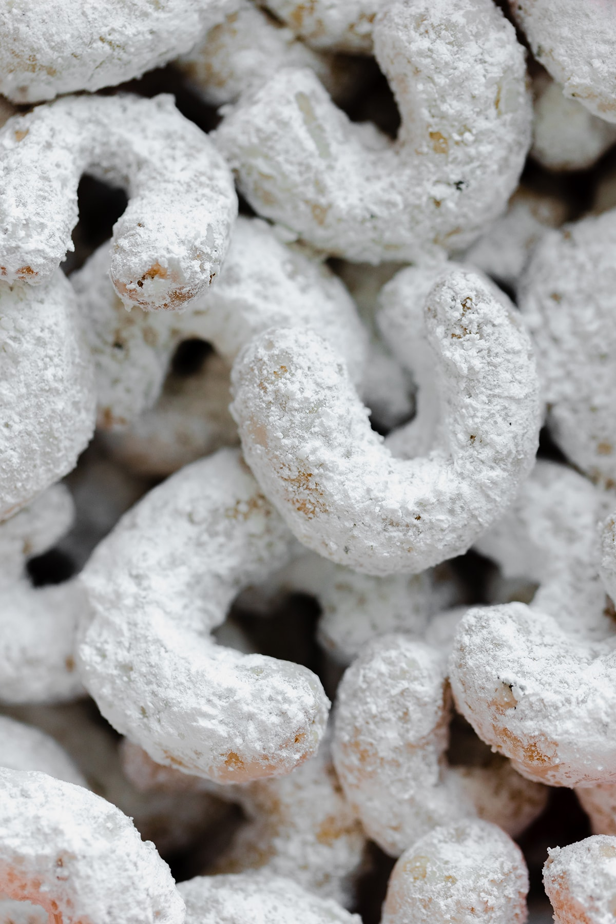 A tight close up of crescent cookies covered with powdered sugar.