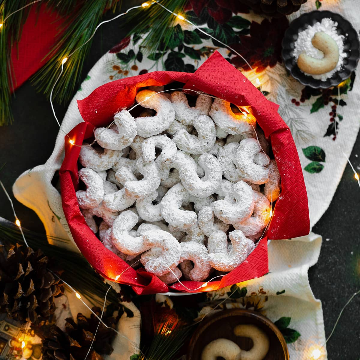 A square photo of Vanilla Walnut Crescent Cookies in a box with a red paper napkin surrounded with fairy lights, pine cones, and a pine branch