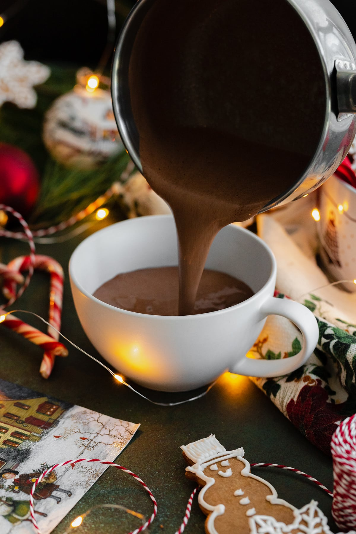 A pouring shot of hot chocolate being poured from a small pot into a white mug.