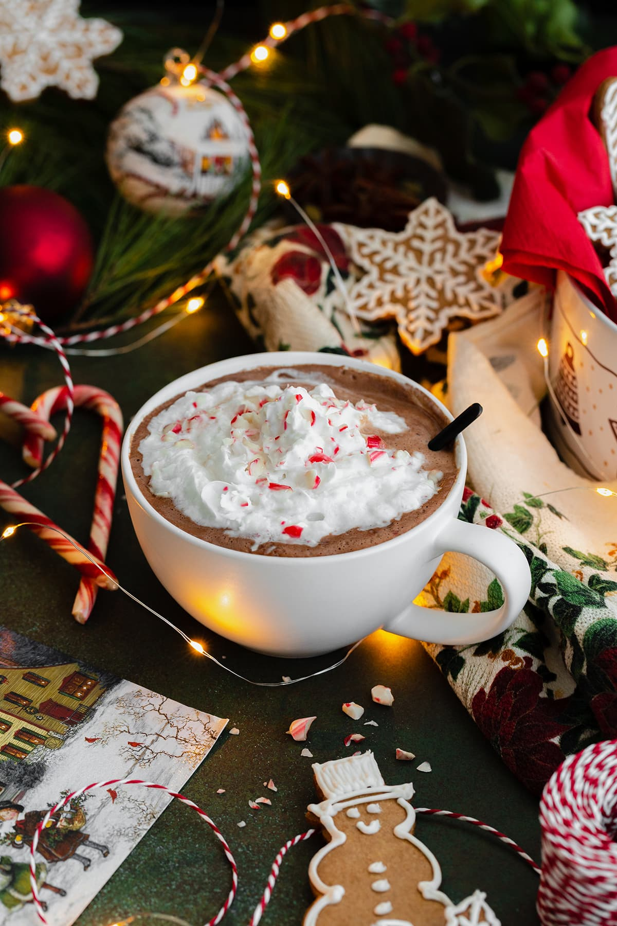 Peppermint hot chocolate in a white cup topped with whipped cream and crushed candy cane. Spoon inside the cup on the right side. Gingerbread cookies aranged around the cup. Dark green background.