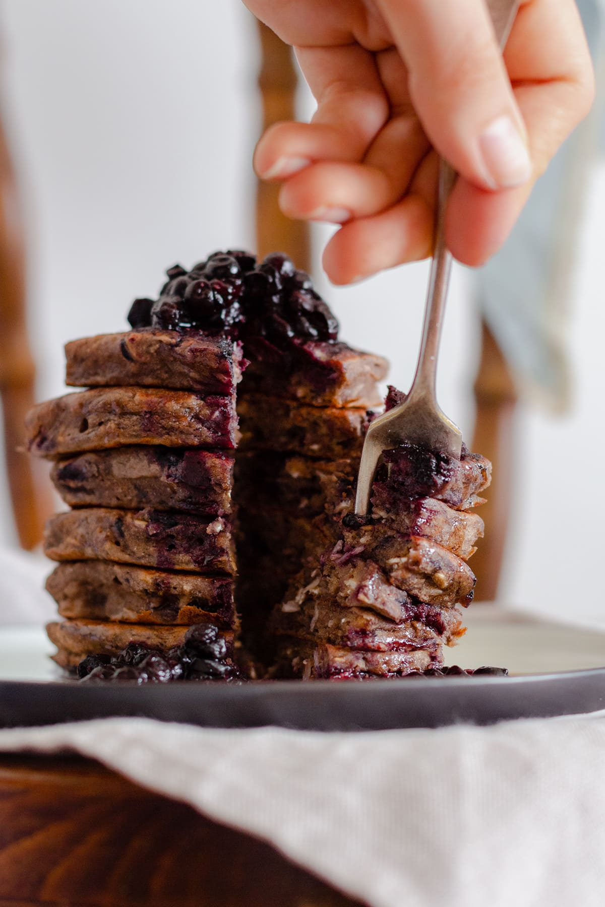 Buckwheat banana blueberry pancakes stacked on a beige plate on a chair. A hand scooping a piece of the layers with a fork.