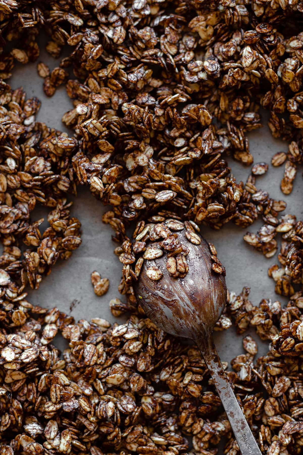 Granola before baking with a spoon covered with the oats and the carob mixture in the middle.