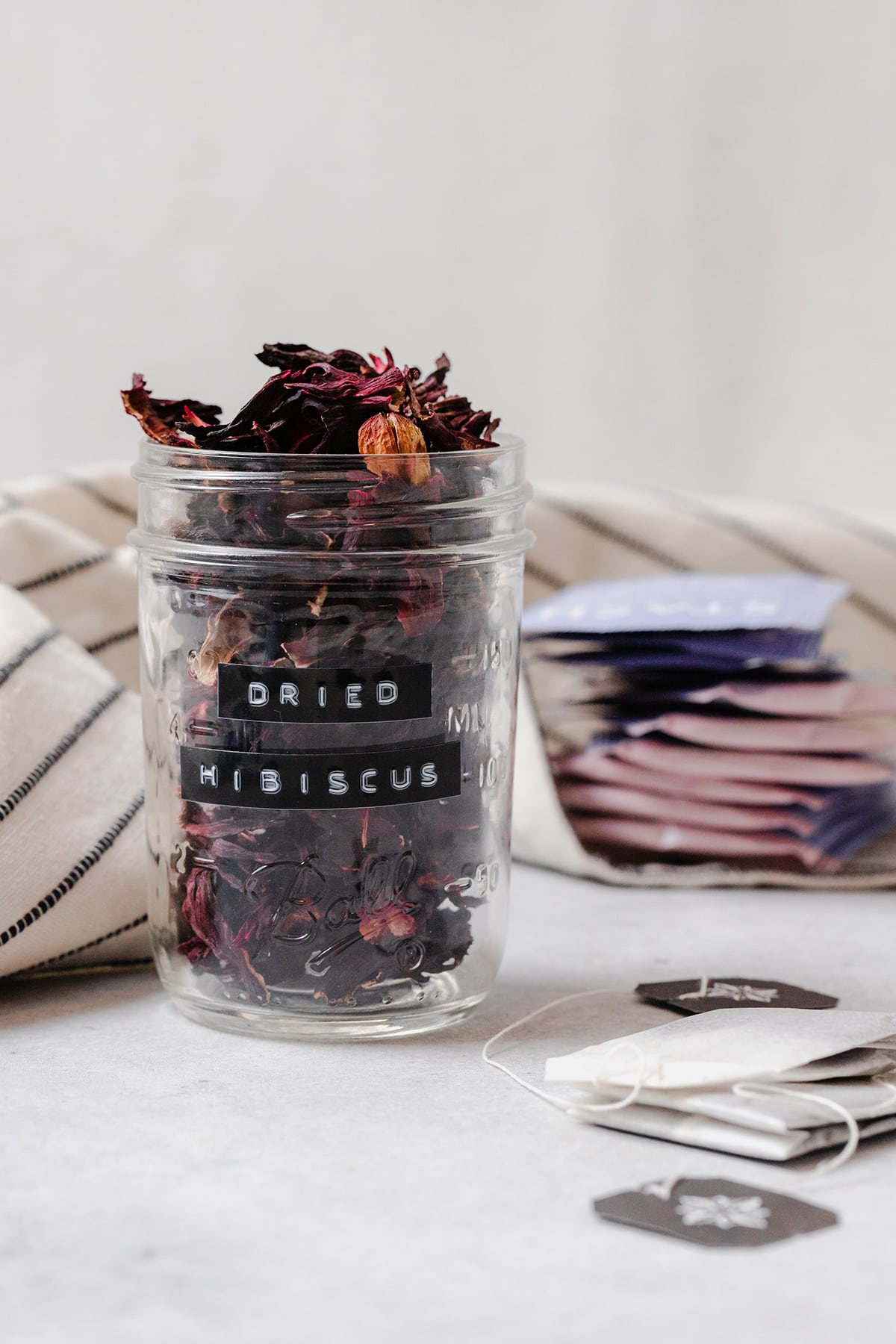 Dried hibiscus flower in a glass jar. On a light grey background with loose tea bags on the right side.