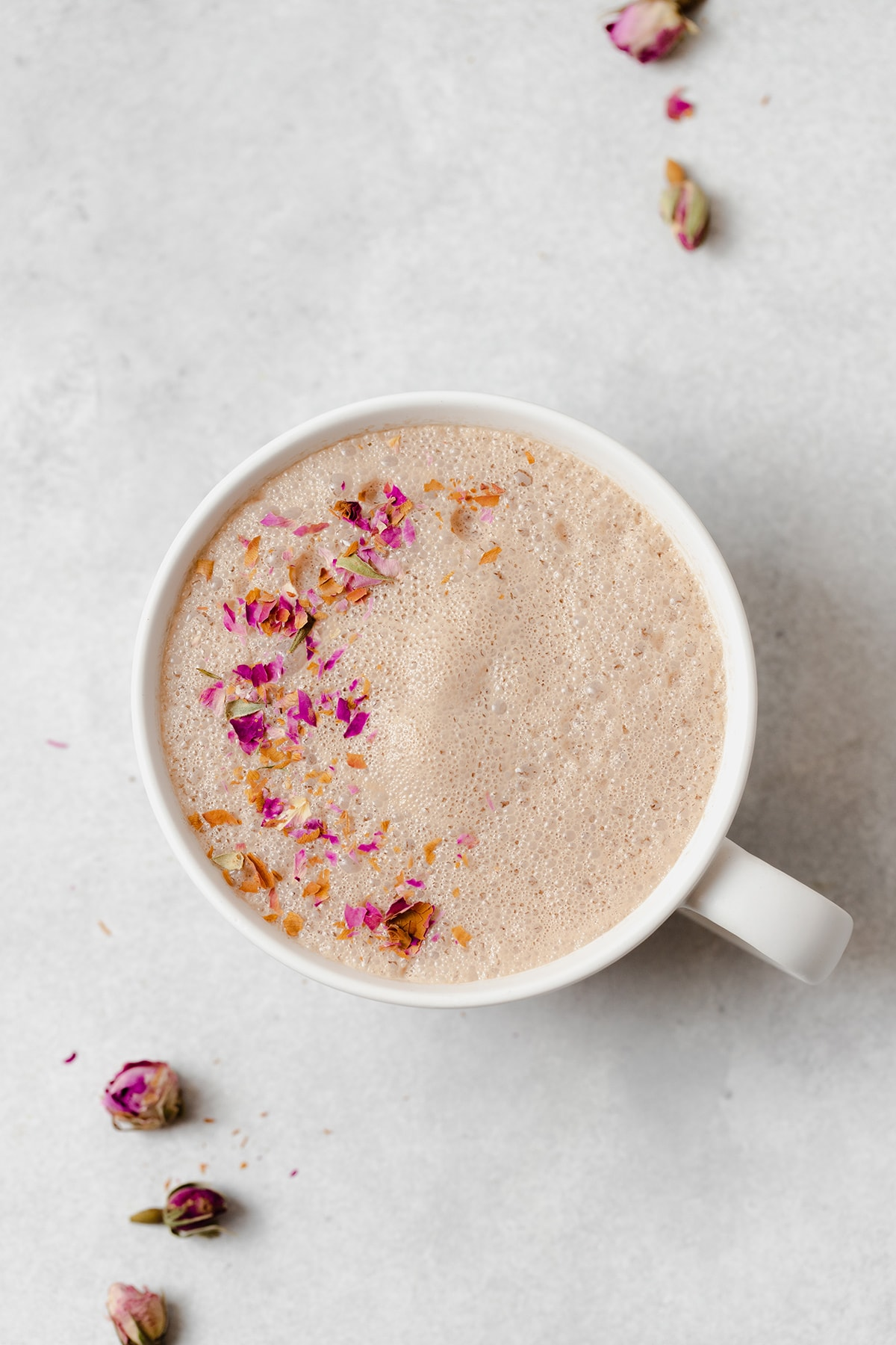Hibiscus earl grey latte in a white mug on a light grey background. Garnished with crushed dried rose petals.