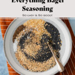 Everything bagel seasoning in a glass jar on a blue table with three bagels in the background and an orange napkin on the right.