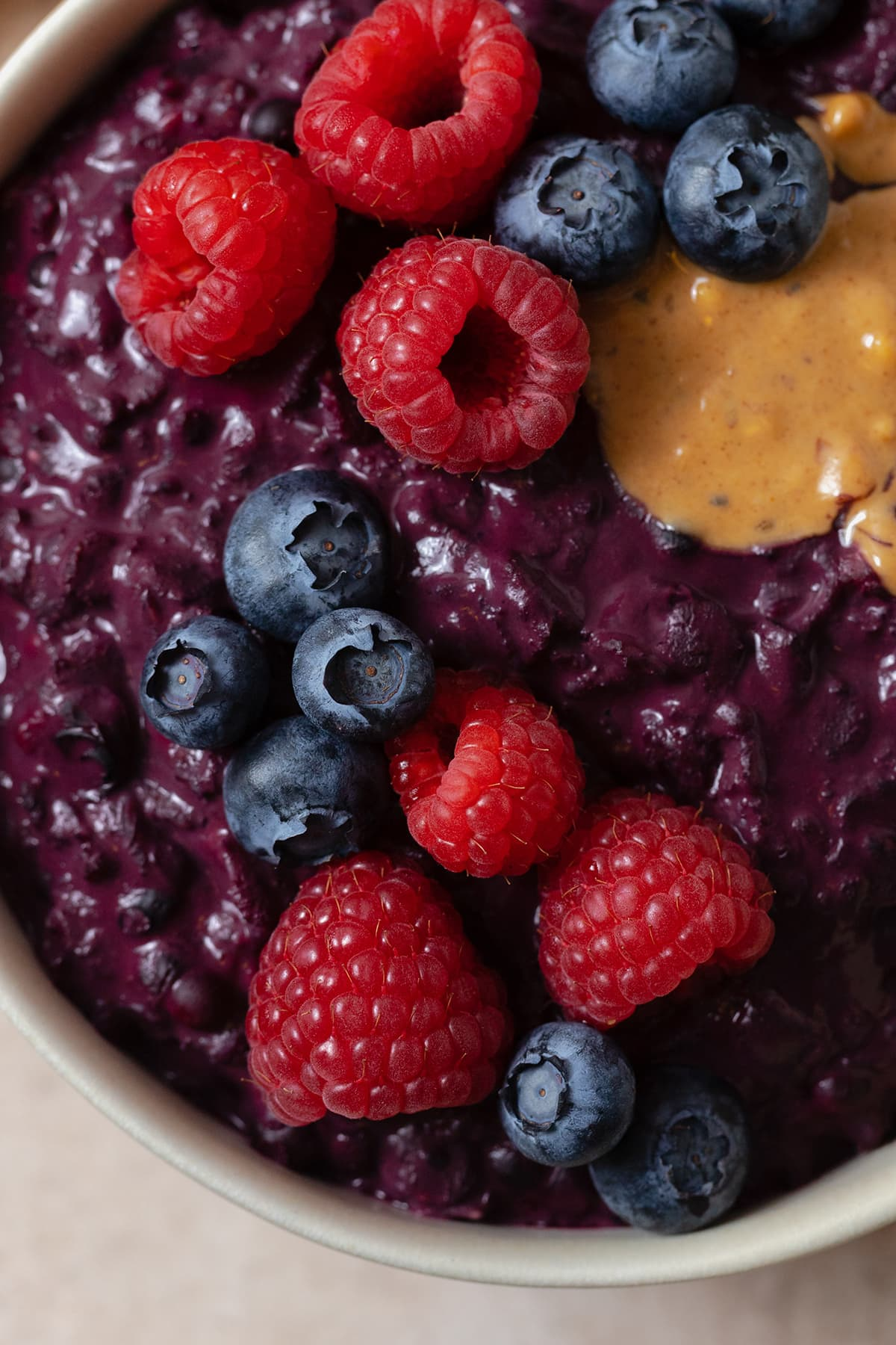 A close up of Maqui Berry oatmeal topped with berries and peanut butter.