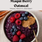 Deep purple oatmeal with maqui berry in a beige bowl on a light orange background. Served topped with raspberries, blueberries, and a spoonful of nut butter. Recipe title in picture.