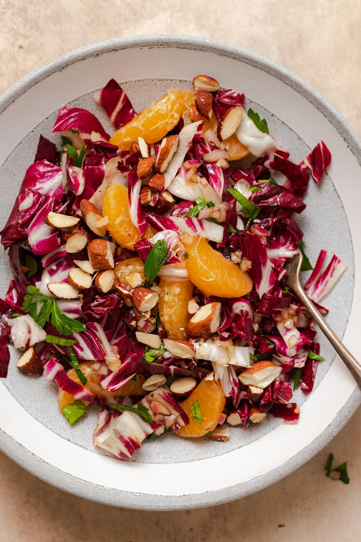 A close up shot of the Radicchio Clementine Salad shown on a shallow grey bowl with a white stripe along the edge. Fork resting on the right side of the bowl in the salad.