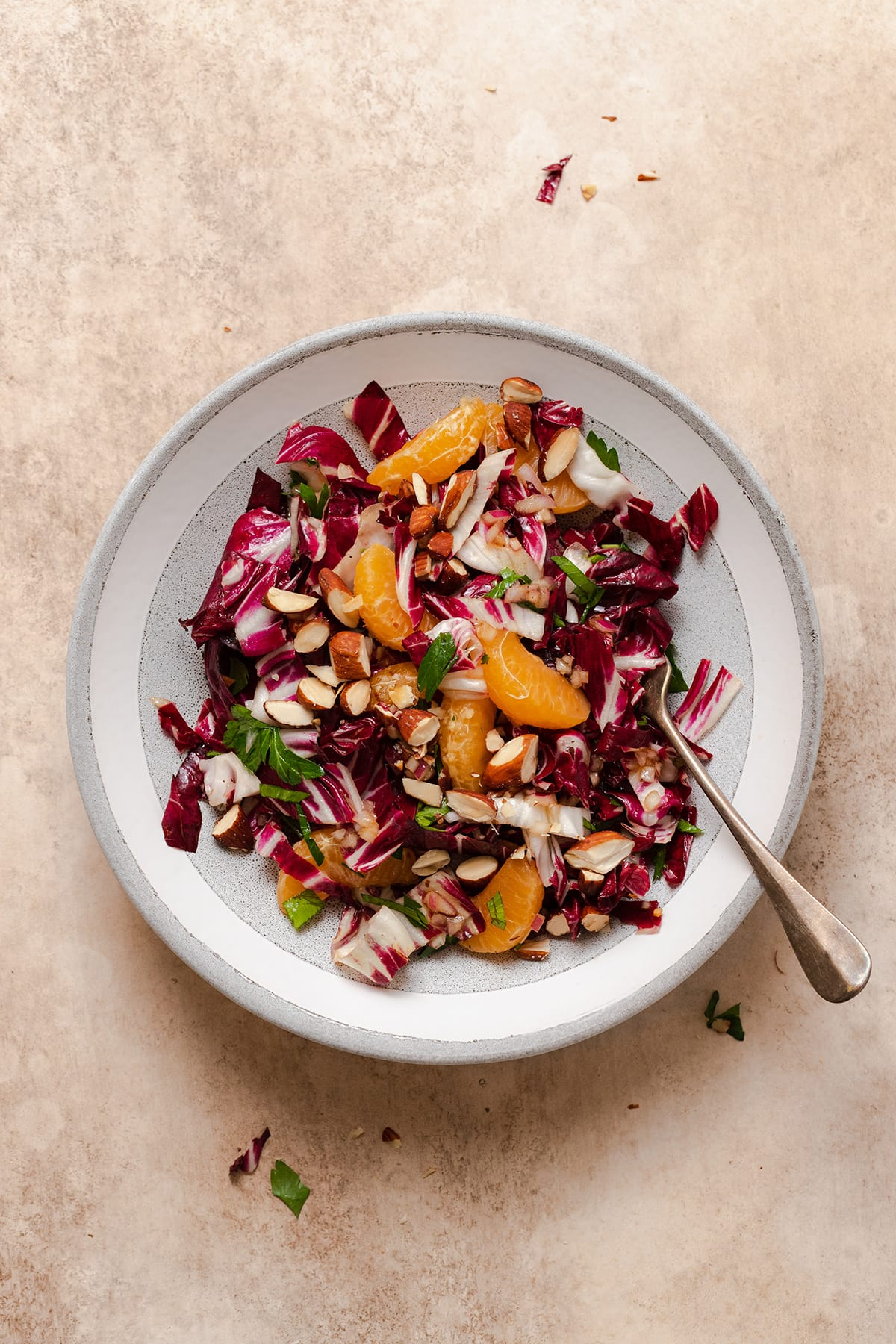 Radicchio Clementine Salad shown on a shallow grey bowl with a white stripe along the edge. Fork resting on the right side of the bowl in the salad.