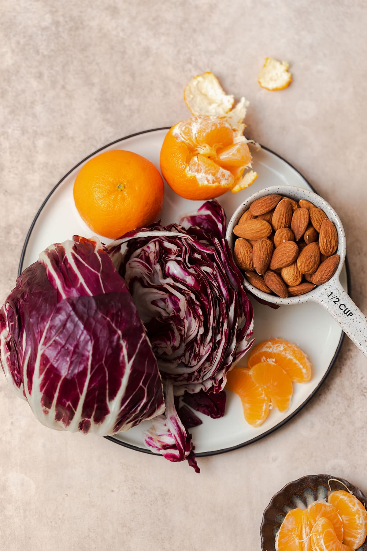 Ingredients for the clementine salad laid out on a plate. Whole clementines, whole almonds, and a whole head of radicchio.
