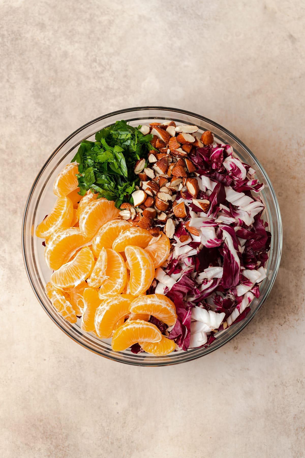All ingredients for the clementine salad laid out in a glass bowl. There is chopped radicchio, chopped almonds, chopped parsley, and clementine pieces.