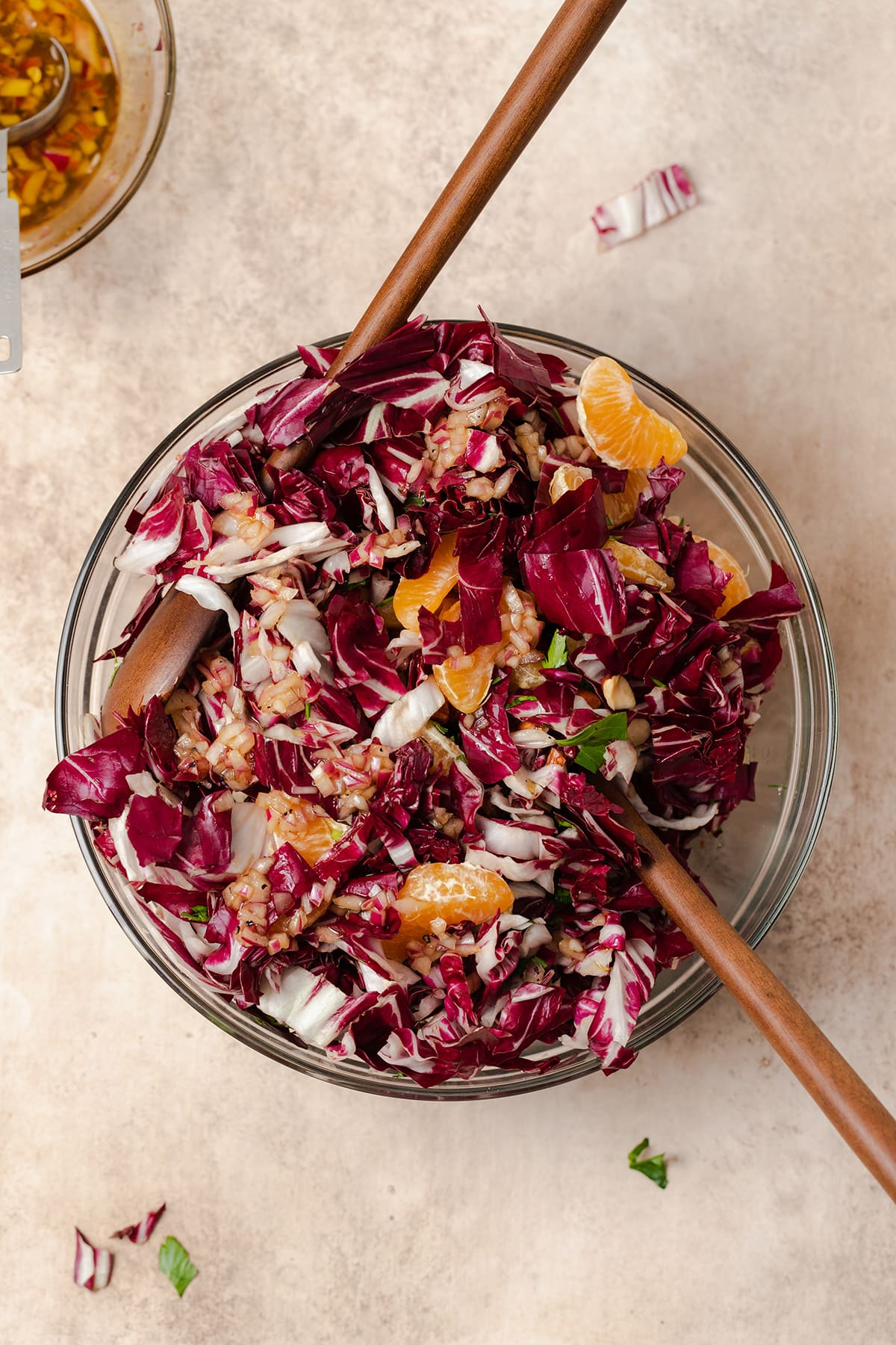 Radicchio Clementine Salad shown in a glass bowl with wooden salad spoons inserted in the bowl.