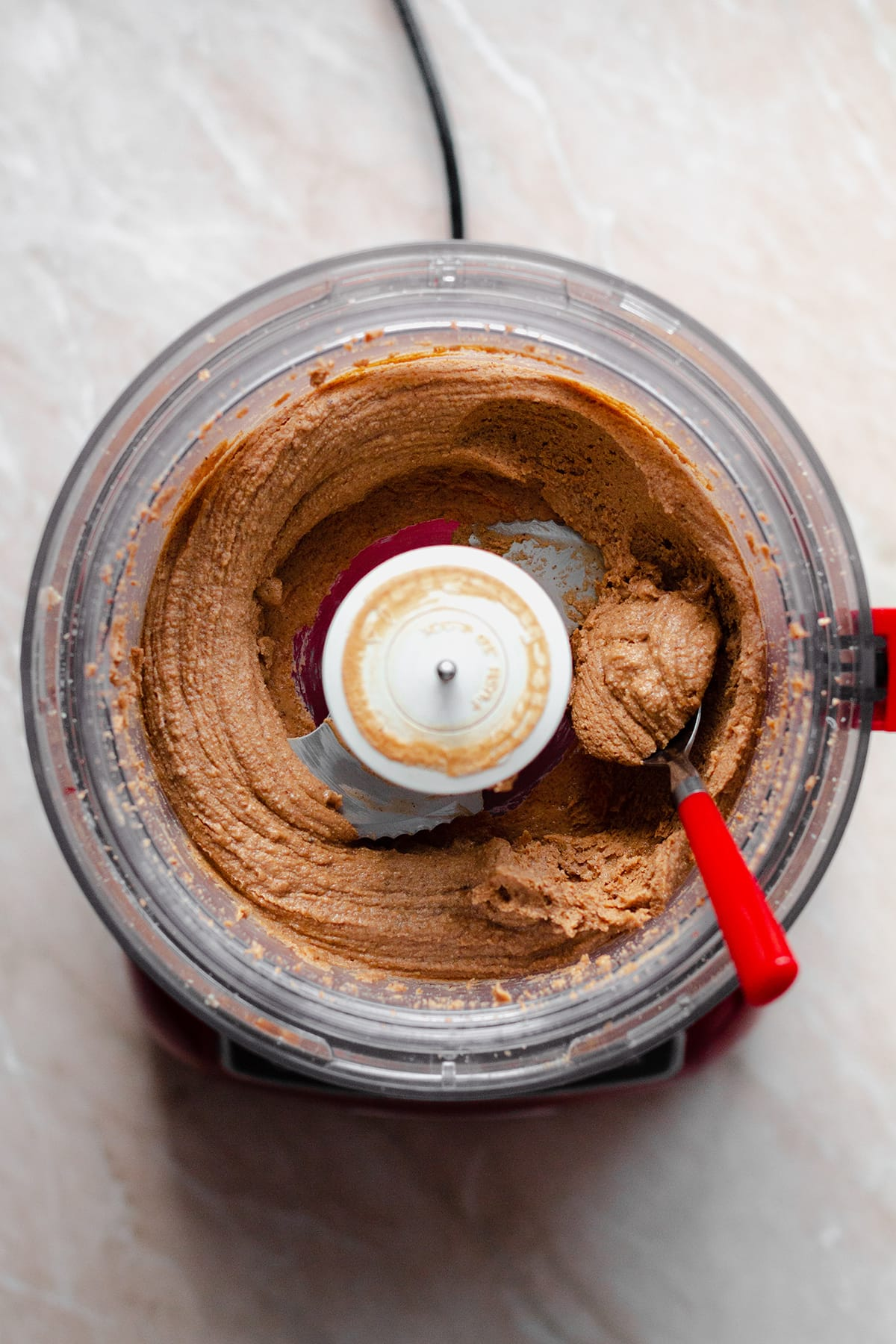 Salted Caramel Nut butter in a food processor with a red spoon on the right.