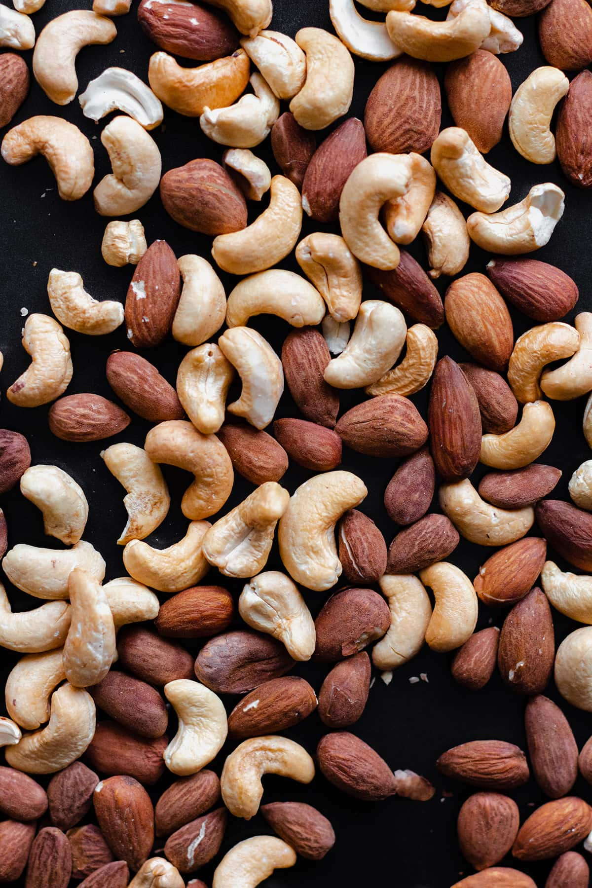 Cashews and almonds on a black background.
