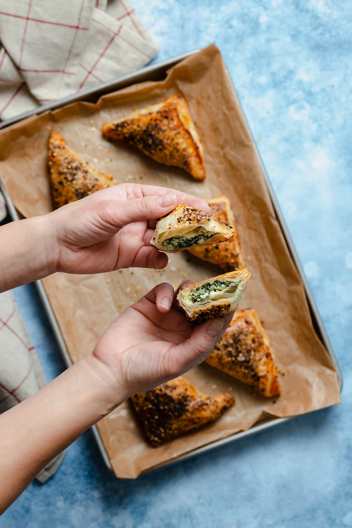Spinach and Feta Puff Pastry Triangles on a baking sheet lined with parchment paper. Hands holding one triangle cut in half.