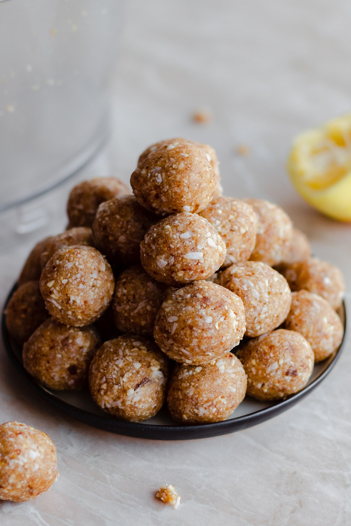 A photo of Zesty Lemon Coconut Energy Balls stacked up on a plate. Light marble background. Lemon in the background on the right side.