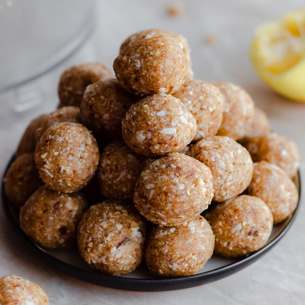 Coconut Energy Balls stacked up on a plate. Light marble background.