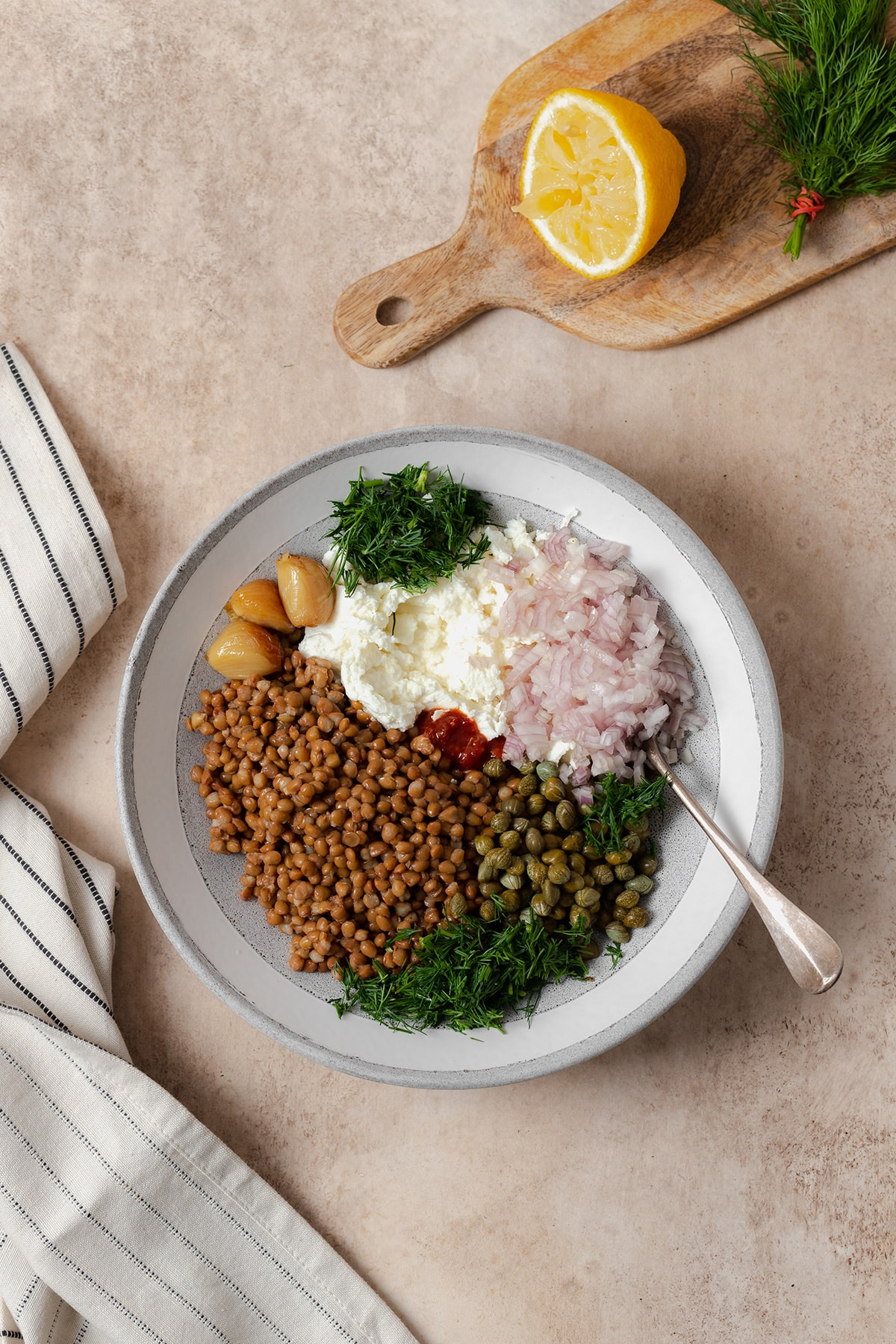 Ingredients shown in a grey bowl. Cooked brown lentils, capers, olive oil, half a lemon, a block of soft goat cheese, half a shallot, a bunch of fresh dill, roasted garlic, and garlic chili sauce.