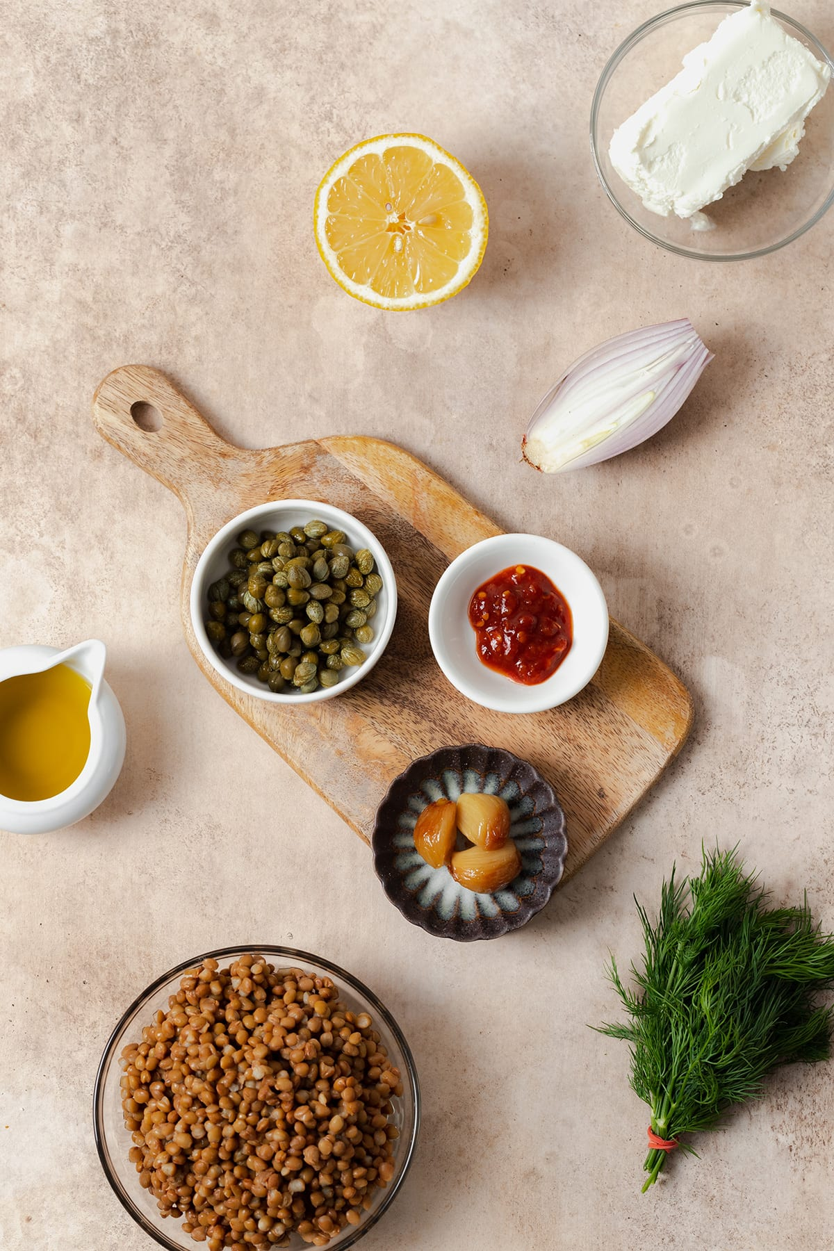 Ingredients laid out on a beige background. Cooked brown lentils, capers, olive oil, half a lemon, a block of soft goat cheese, half a shallot, a bunch of fresh dill, roasted garlic, and garlic chili sauce.