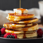 Pancakes shown stacked on a black plate with butter on top and maple syrup being poured on.