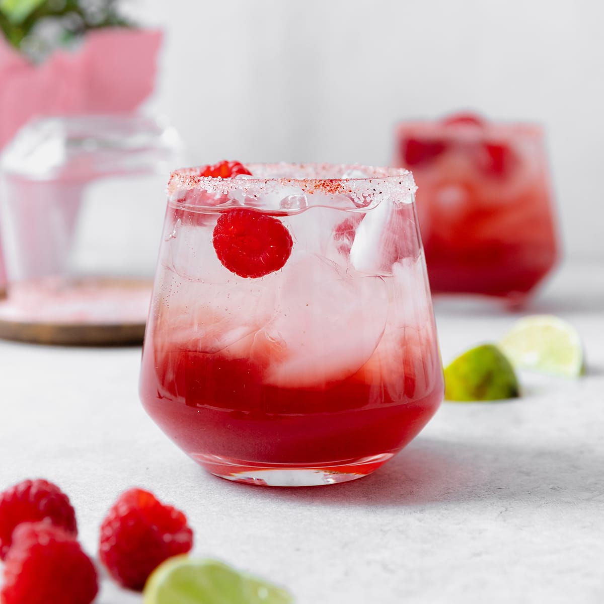 Raspberry margarita shown in a double old-fashioned glass with ice and fresh raspberries. On grey background.
