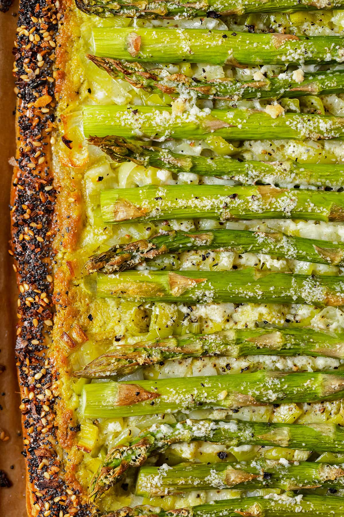 A close up of the filling and the left edge of the tart. Asparagus, goat cheese pesto spread, pecorino cheese with golden bits from baking. Crust sprinkled with everything bagel seasoning.