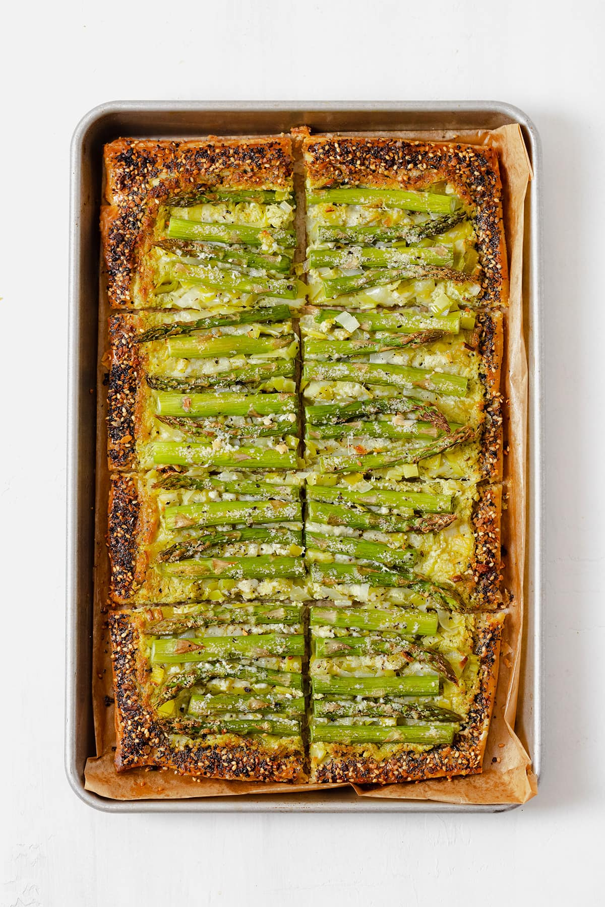 An asparagus tart on a baking sheet lined with parchment paper, cut into 8 squares.