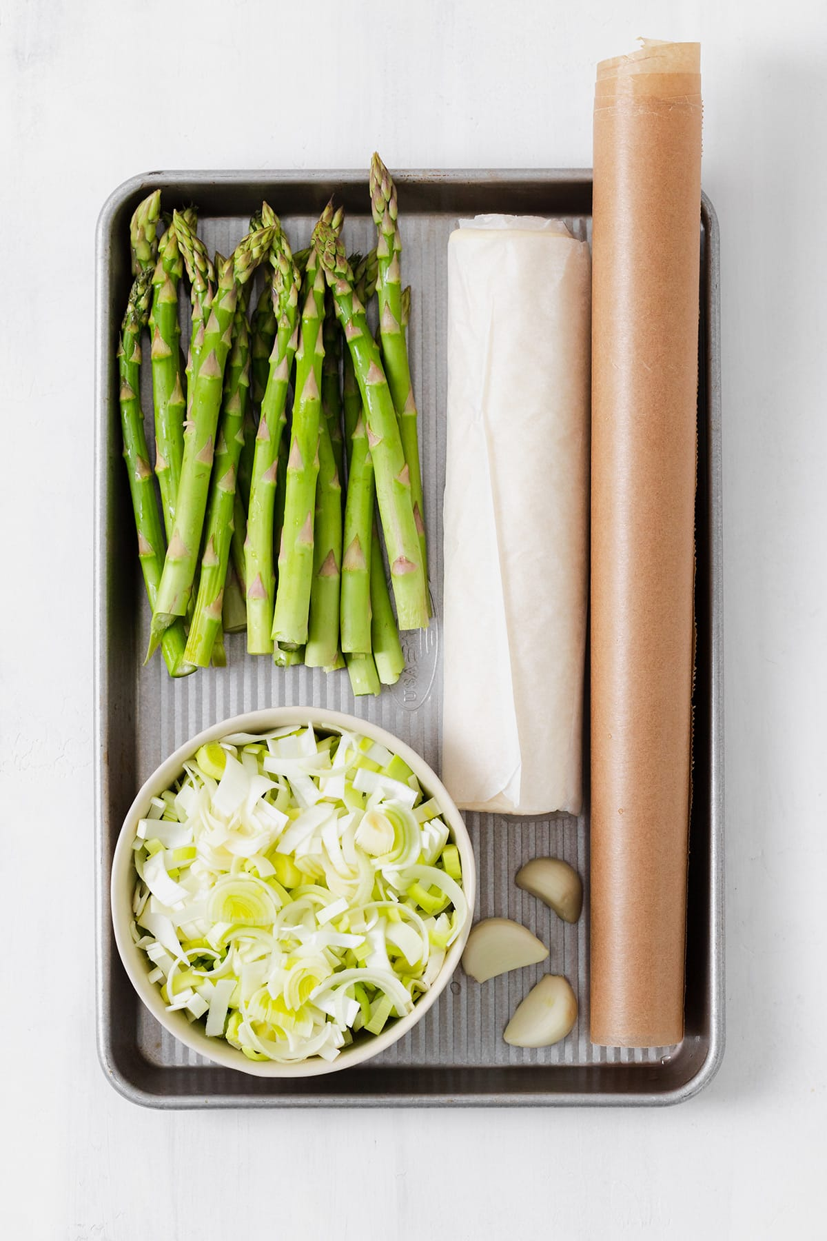 Ingredients for asparagus tart laid out on a baking sheet - asparagus, chopped leek, garlic cloves, puff pastry, and parchment paper