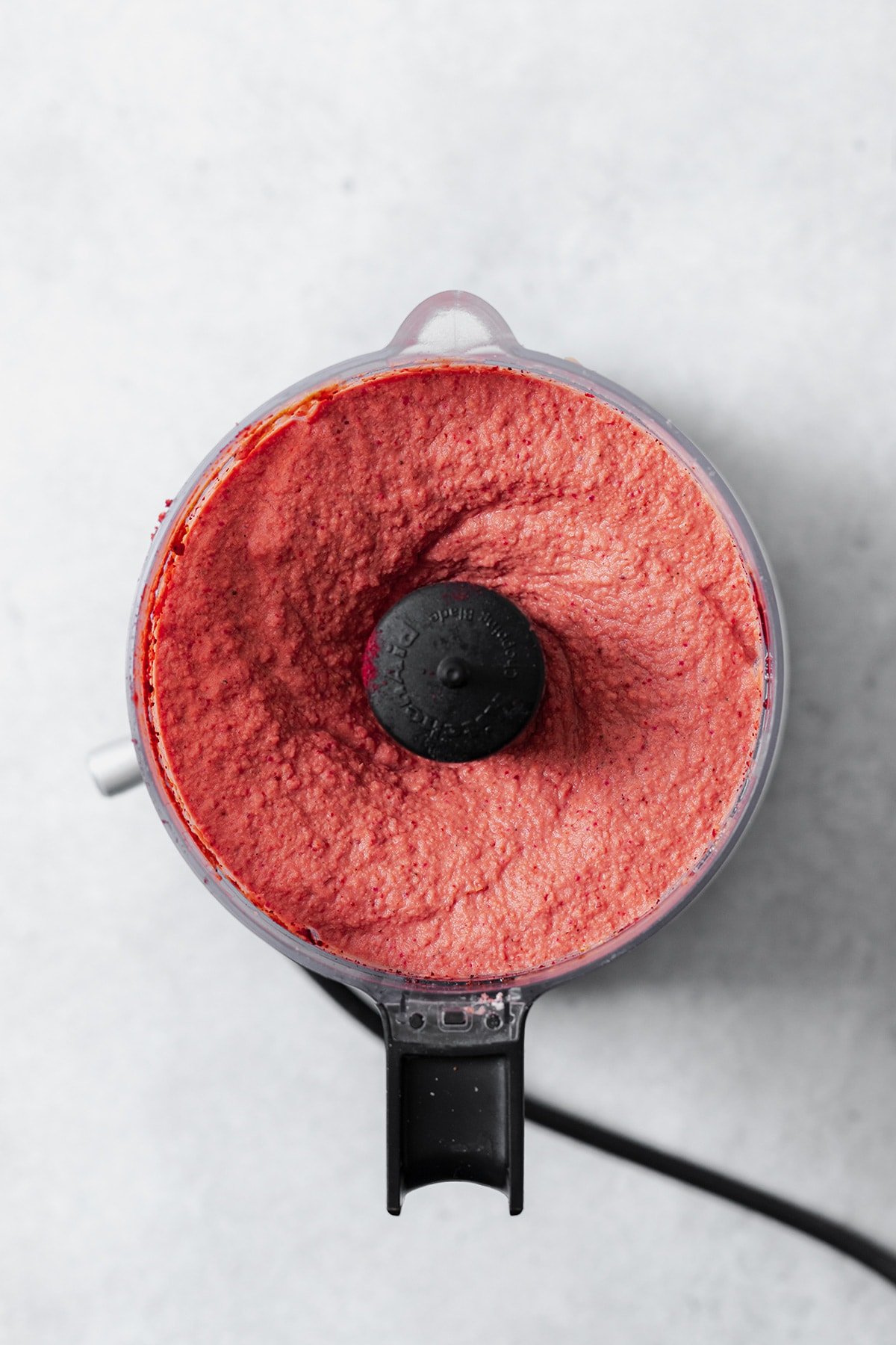 A photo of a small food processor full of the beet hummus after it's been blended.