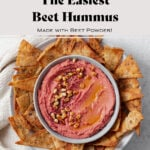"""Beet hummus shown in a grey bowl on a grey plate surrounded by homemade pita chips. Grey background with a beige tea towel on the left of the bowl. Photo says """"The Easiest Beetroot Hummus"""""""