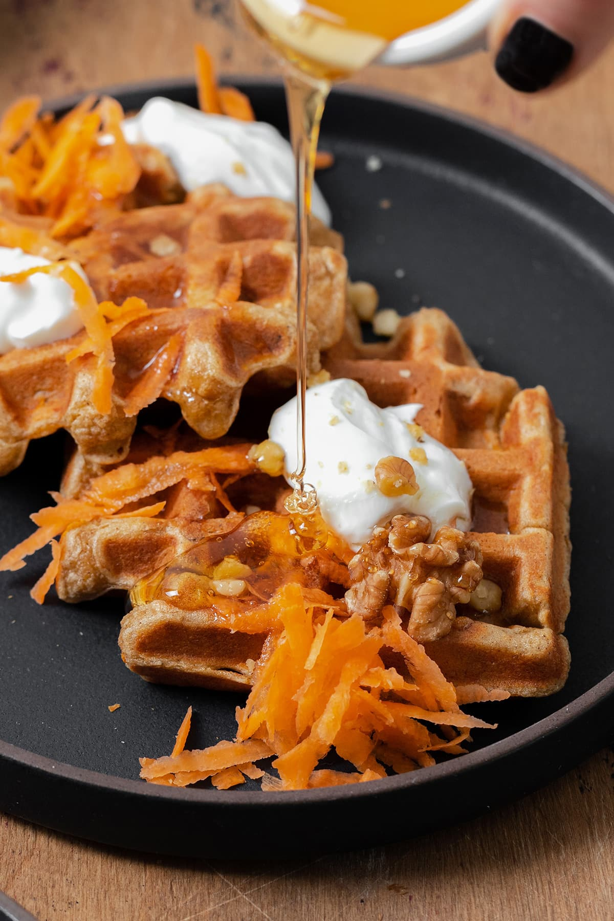A photo of a hand holding a small bowl of honey and pouring it over two carrot cake waffles on a black plate topped with grated carrots, dollops of greek yogurt, and walnuts.