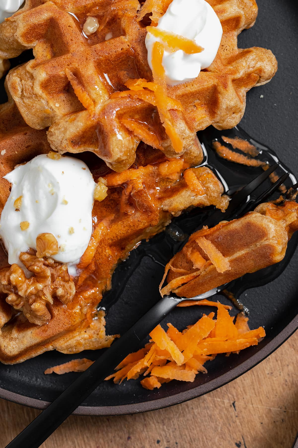 A close up photo of two carrot cake waffles shown on a black plate topped with greek yogurt, honey, grated carrots, and walnuts. A black fork cut a bite-sized piece from one waffle.