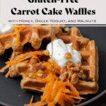 A photo of honey being poured over two carrot cake waffles on a black plate topped with grated carrots, dollops of greek yogurt, and walnuts.