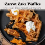 Two carrot cake waffles shown on a black plate topped with greek yogurt, honey, grated carrots, and walnuts. A black fork cut a bite-sized piece from one waffle.