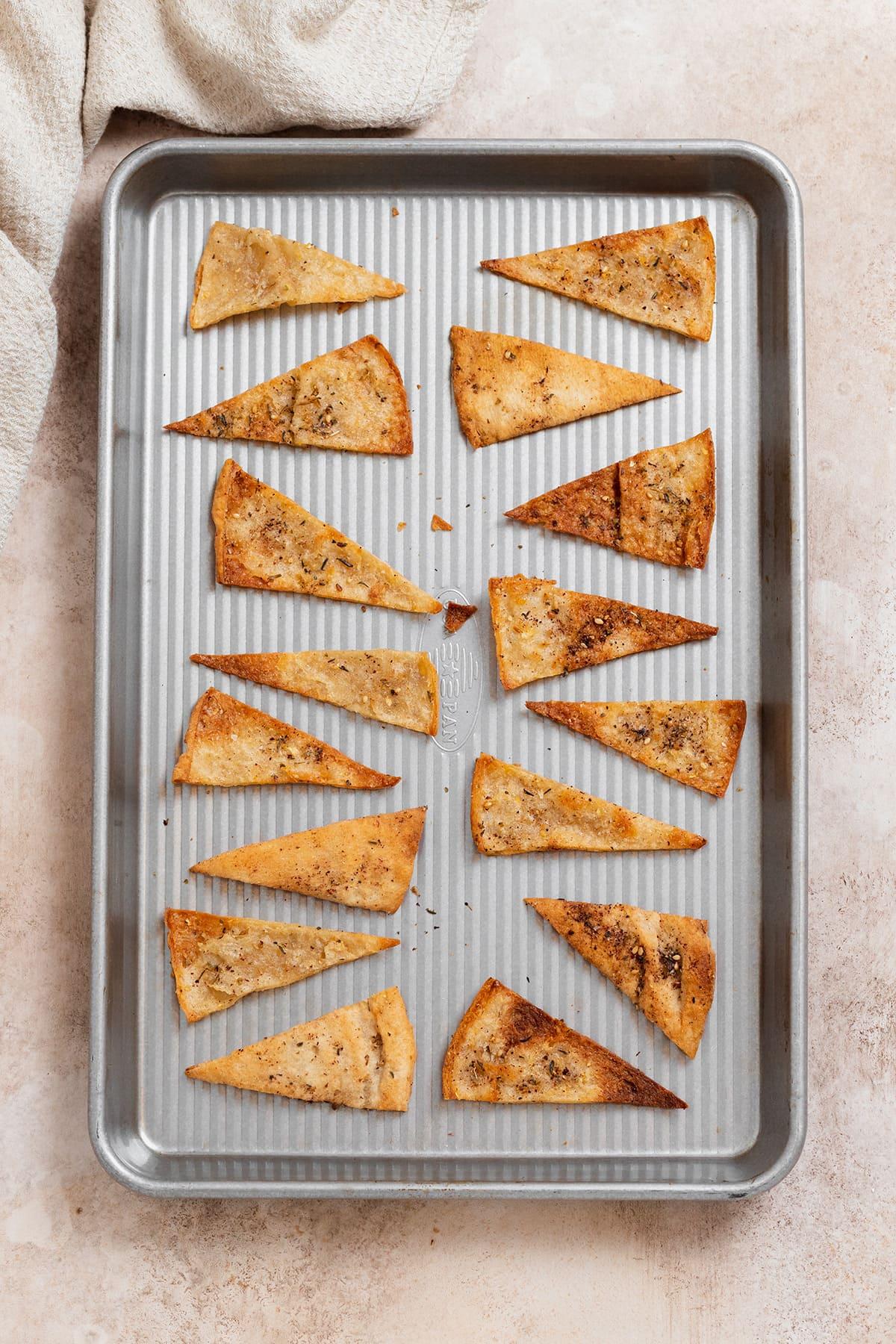 Homemade pita chips on a silver baking sheet.