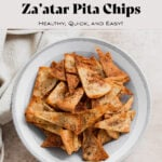 Homemade pita chips in a grey bowl on a beige background with a beige tea towel in the top left corner.