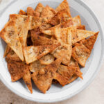 A close up photo of homemade pita chips in a grey bowl on a beige background.