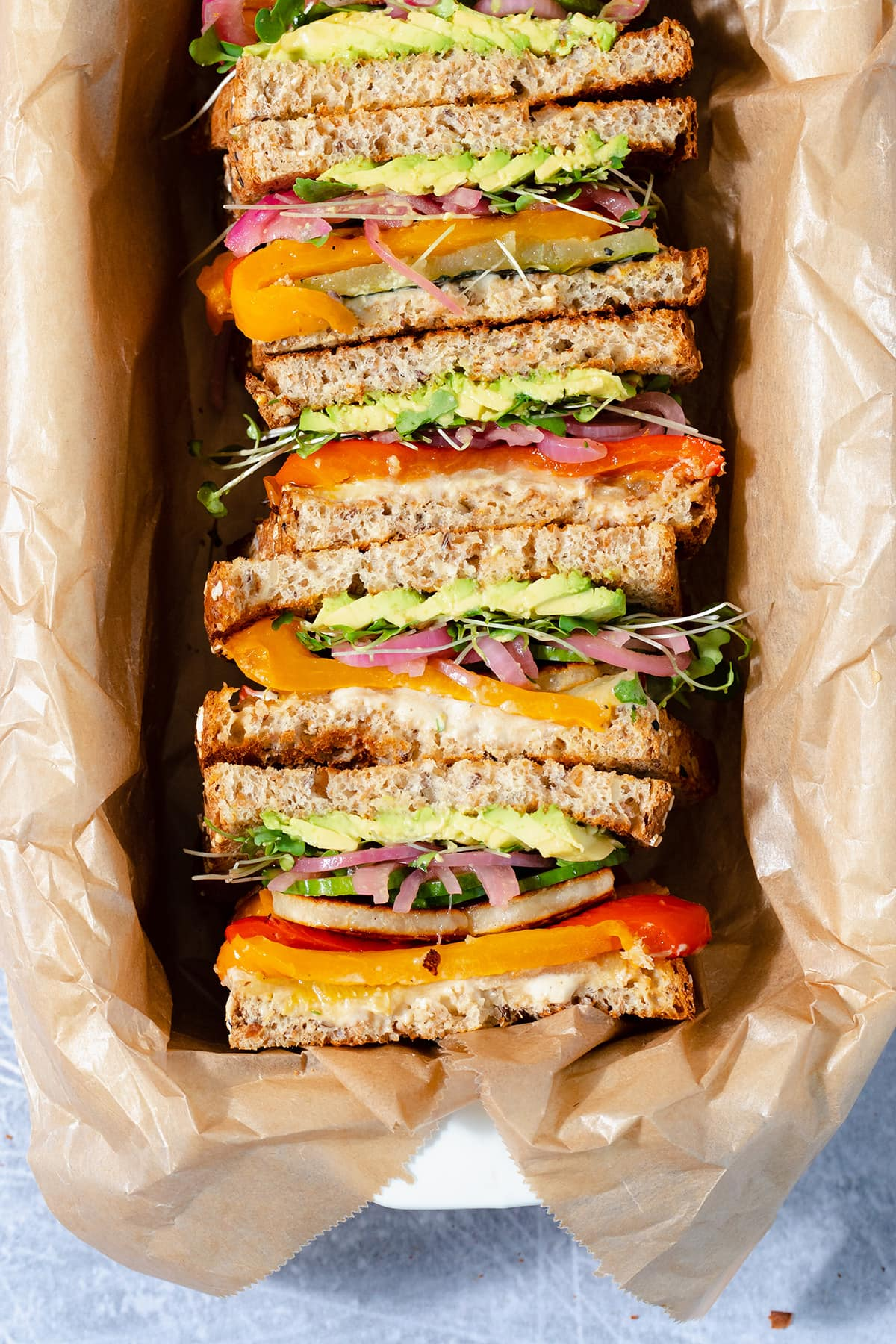 Halloumi sandwiches cut in half and arranged cut side up in a baking dish lined with parchment paper.