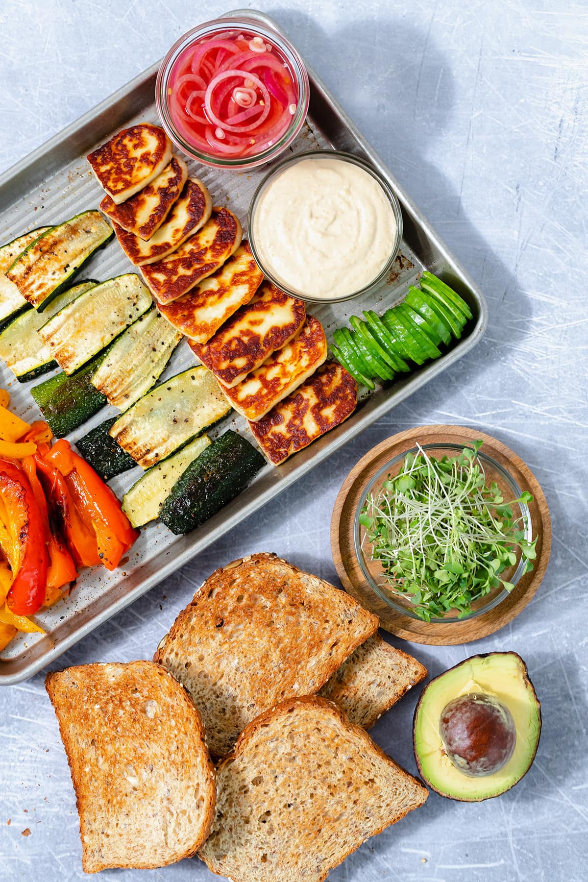 All the ingredients for halloumi sandwich all laid out on a baking sheet and a steel background.
