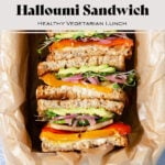 Halloumi sandwiches cut in half and arranged cut side up in a baking dish lined with parchment paper. Text overlay of the recipe name.