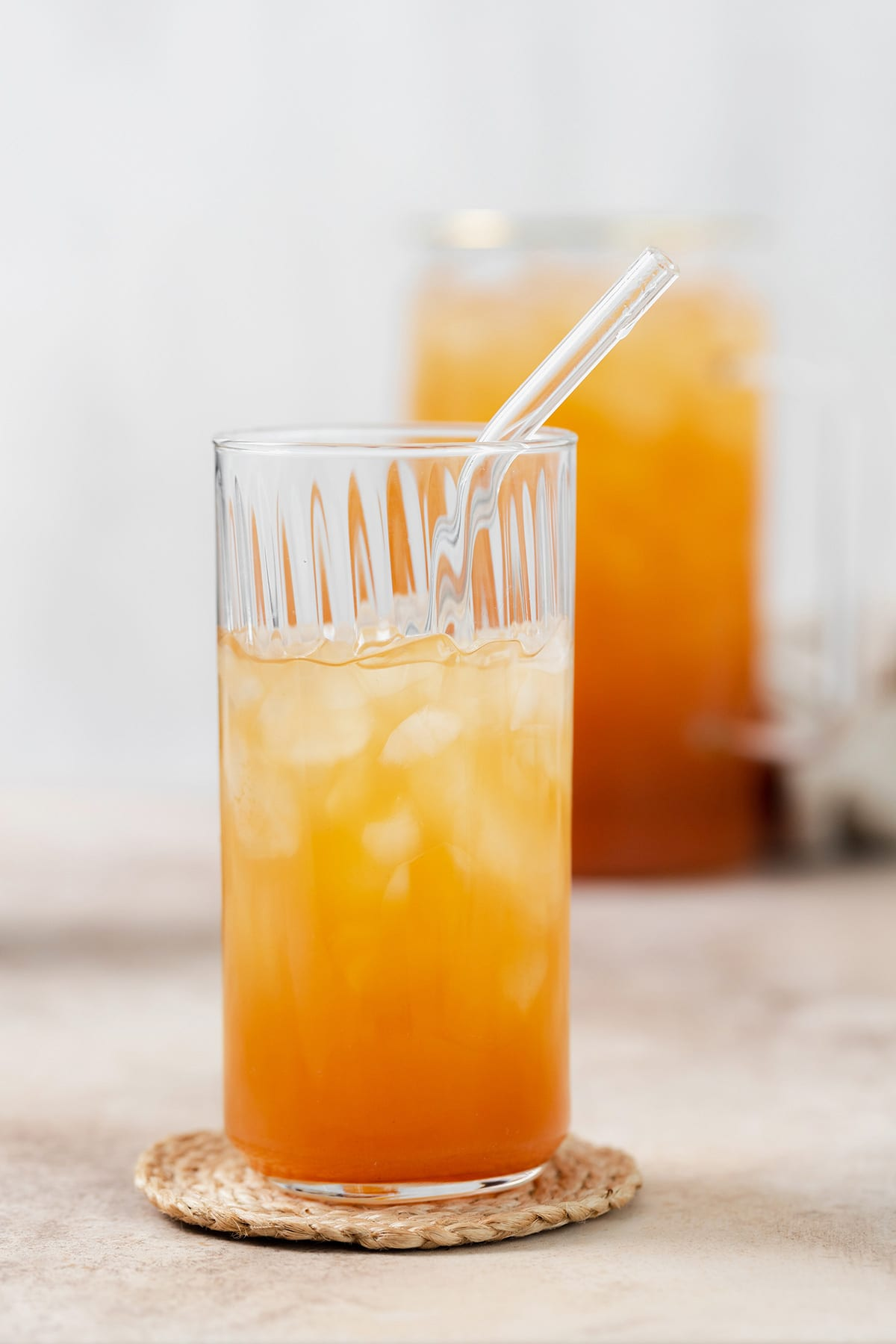 Iced Guava Black Tea shown in a tall glass with ice and a glass straw on beige background. Glass is 3/4 full. More glasses and a jug full of iced tea partially in the frame on both left and right. Beige tea towel blurry in the background.