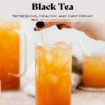 Iced Guava Black Tea shown in a tall glass with ice and a glass straw on beige background. More glasses and a jug full of iced tea partially in the frame on both left and right. Beige tea towel blurry in the background. A hand reaching for the straw from the right.